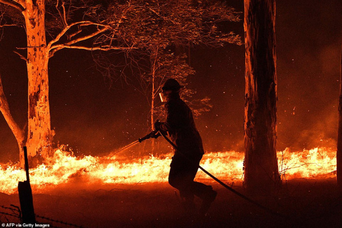 This picture taken on December 31, 2019 shows a firefighter in an effort to secure neighboring houses from blazes near the town of Nowra on the NSW south coast