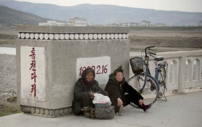 These North Korean citizens are relaxing because they are tired from biking for a long time (often hours) to work and have stopped to rest.