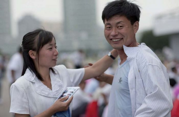 North Koreans are expected to dress formally while out in public. When asked if they could be photographed while dancing in a park, this woman tried to fix the man's shirt before the photo was taken.