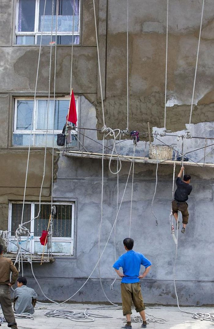 North Korea doesn't enforce safety standards on work sites like this (putting the workers in harms way). Yet, it is forbidden to photo these circumstances.