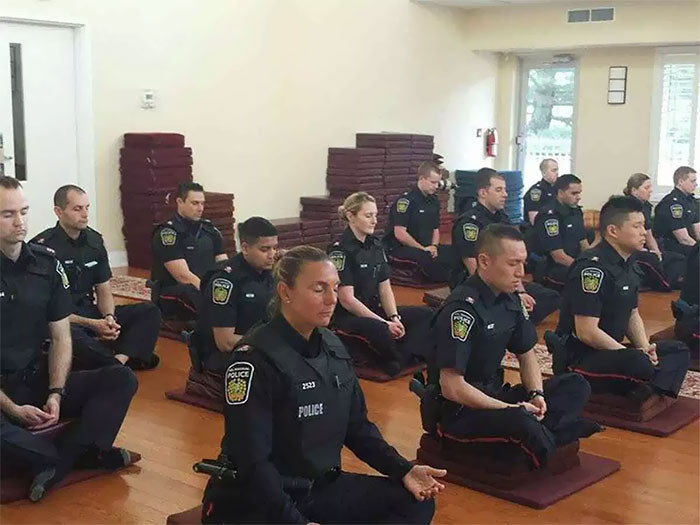 16. Before starting their day, these Candian Police Officers are meditating in order to achieve a mentally clear and emotionally calm and stable state.
