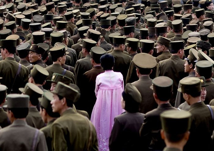 This woman is standing in the middle of a group of soldiers. It is illegal to takes photos of the military in North Korea.