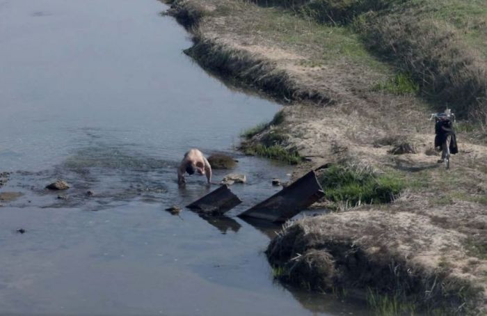 This man is bathing himself in a river near his home- displaying the poverty in the country.
